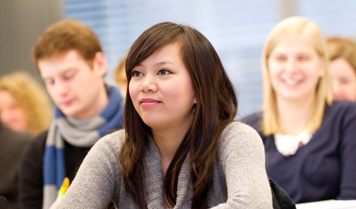 Female student sitting with other students in the lecture hall